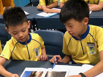 A P5 pupil volunteer guiding a pupil during the Reading Buddy Prog - new.jpg