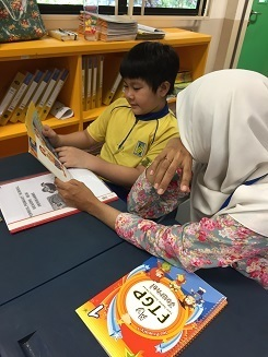 Parent volunteer guiding the pupil during the Reading Mum Prog - new.jpg